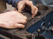Repair car engine. Car mechanic repairing an internal combustion engine Stock Image