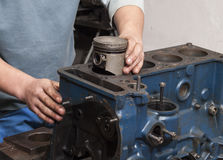 Repair car engine. Car mechanic repairing an internal combustion engine Royalty Free Stock Photography