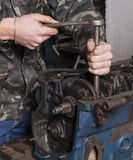 Repair car engine. Car mechanic repairing an internal combustion engine royalty free stock image