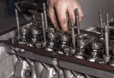 Repair car engine. Car mechanic repairing an internal combustion engine royalty free stock photo