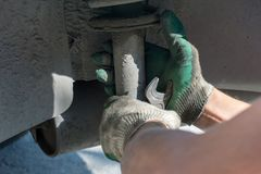 Repair of the car suspension. Gloved hand. Replacing the shock absorber strut stock photo