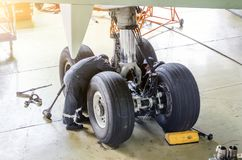 Repair of the chassis landing gear of the aircraft, two technicians of mechanics at work in the hangar. Stock Photos