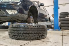 Repair and check car in repair shop. An experienced technician repairs the faulty part of the car. I change tires. Replacing winter tires on summer tires in a stock photo