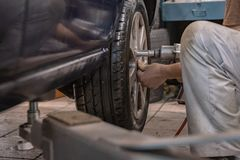 Repair and check car in repair shop. An experienced technician repairs the faulty part of the car. I change tires stock photo