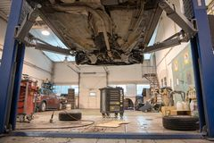 Repair and check car in repair shop. An experienced technician repairs the faulty part of the car. I change tires royalty free stock image