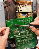 Repair of circuit board. Technician repairs electronic circuit board of tube television with iron soldering and tin wire Royalty Free Stock Photos