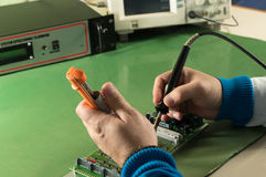 Repair circuit board with soldering iron and pump in  laboratory Stock Image