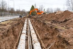 Excavator dug a trench for renew old pipes. Repair of city communications. An orange excavator dug a trench for renew old pipes stock photography