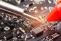 Repair of computer board soldering. Selective focus Royalty Free Stock Photo