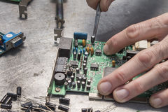 Repair of computer hardware. Modem repair. Replacement of the capacitor. An employee at an electric service while at work. Repair of computer hardware. Modem Royalty Free Stock Image