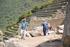 Repair and conservation on Machu Picchu. In the photo, workers are repairing the floor of one of the more traveled part on Machu Picchu using tools that produces Stock Photos