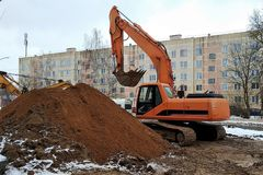 Repair construction works, the hydraulic excavator on caterpillar to the course of orange color, a big heap of the earth, work in. The city against the royalty free stock images