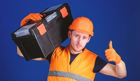 Repair consultation concept. Man in helmet, hard hat holds toolbox and shows thumb up gesture, blue background. Worker. Repairer, repairman, builder on royalty free stock photography
