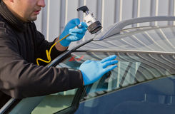 Repair crack in windshield. Service agent  repairs danagerous crack in windhield on location without replacement glass for free, Smart repair Royalty Free Stock Photography