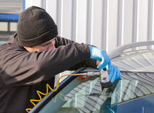 Repair crack in windshield. Service agent  repairs danagerous crack in windhield on location without replacement glass for free, Smart repair Stock Photography