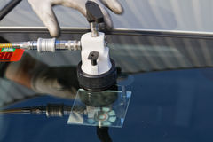 Repair crack in windshield. Service agent  repairs dangerous crack in windshield on location without replacement glass for free Stock Images