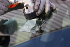 Repair crack in windshield. Service agent  repairs dangerous crack in windshield on location without replacement glass for free Stock Photography