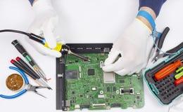 Repair of the digital printed circuit board concept. Repair of the digital printed circuit board of the modern TV in the professional service center. Repair man stock images