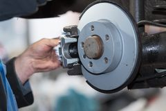 Repair disc brake - hand brake, which have been replaced in the auto repair shop. Repair disc brake - hand brake, which have been replaced in the workshop in the stock photography