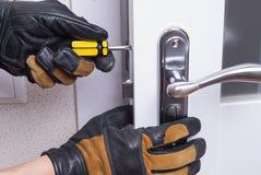 Repair door lock. Handyman repair the door lock in the room royalty free stock images