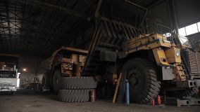 Repair of dump trucks in large garage open pit. Repair of dump trucks in large garage stock footage