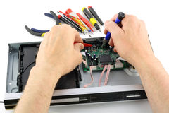 Repair of the DVD Player. The technician repairs a DVD Player. Isolated on white stock photos