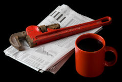 Repair the Economy. A red pipe wrench rests on top of the financial section of the morning newspaper next to a red cup of coffee . Illustrates that it's time to Royalty Free Stock Photography