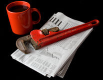 Repair the Economy. A red pipe wrench rests on top of the financial section of the morning newspaper next to a red cup of coffee . Illustrates that it's time to Stock Photos