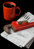 Repair the Economy. A red pipe wrench rests on top of the financial section of the morning newspaper next to a red cup of coffee . Illustrates that it's time to Royalty Free Stock Images
