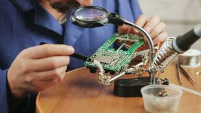 Repair of electrical equipment close-up. Man-an engineer repairing electrical equipment. The engineer considers the Board . A man soldering a circuit Board stock video footage
