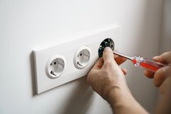 Repair electricity socket man with bare hands. Improper safety or repair of the electrical outlet. With a screwdriver stock images