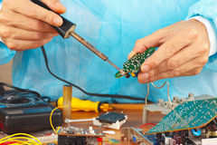 Repair electronic board of device with a soldering iron Stock Image