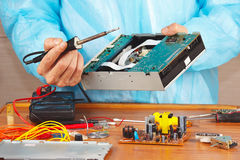 Repair electronic hardware with a soldering iron in service workshop Royalty Free Stock Photography
