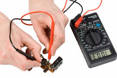 Repair of electronics. With digital multimeter in the white background Stock Photography