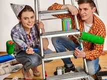 Repair family by happy couple building home using ladder. Stock Photos