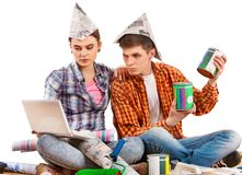 Repair family by happy couple building home using white laptop. Woman and men in newspaper cap renovation apartment. Students do not trust purchases over Stock Image