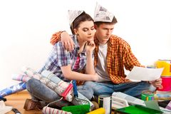 Repair family by happy couple building home using white laptop. Woman and men in newspaper cap renovation apartment. Loan for housing for a couple. They ask Royalty Free Stock Photos
