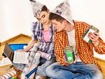 Repair family by happy couple building home using white laptop. Woman and men in newspaper cap renovation apartment. Purchase of furniture through Internet Royalty Free Stock Images