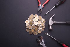 Repair or fixing money or financial concept. Industrial tool and. Pile of coin on black stone board background. Top view for business use Royalty Free Stock Images