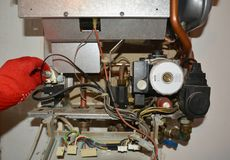Repair of a gas boiler, setting up and servicing gas boiler by repairman. Close up royalty free stock images