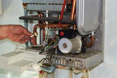 Repair of a gas boiler, setting up and servicing by a service department.  royalty free stock images