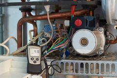 Repair of a gas boiler, setting up and servicing by a service department. Adjustment of gas pressure by manometer royalty free stock images