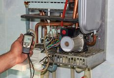Repair of a gas boiler, setting up and servicing by a service department. Adjustment of gas pressure by manometer stock photos