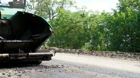 Repair of a highway, on the road there is a special technique for laying a new fresh asphalt pavement, covering . Road stock video
