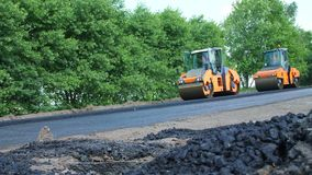 Repair of a highway, roller compactor machine and asphalt finisher laying a new fresh asphalt pavement, covering on one stock video