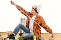 Repair home man holding paint roller for wallpaper. Royalty Free Stock Image