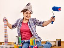 Repair home woman holding paint roller for wallpaper. Stock Images