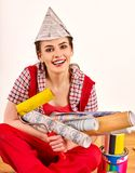 Repair home woman holding paint roller for wallpaper. Aggressive screaming girl in newspaper cap renovation apartment on . Tired of work as a student. She stock image