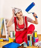 Repair home woman holding paint roller for wallpaper. Repair home women holding paint roller for wallpaper. Aggressive screaming girl in newspaper cap stock photo