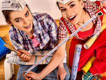 Repair home women holding construction measuring tape wallpaper. Royalty Free Stock Photos